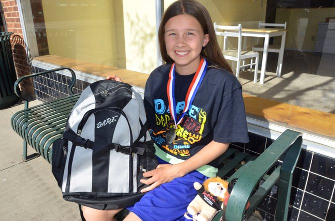 Emaleigh Papierski opens up her backpack, provided by the program Drug Abuse Resistance Education, to reveal the many prizes it includes. Papierski, who recently finished fifth grade at Sunset Elementary School, won the local essay contest for students of DARE, as well as at the state level. She will read her winning essay at a DARE conference in Breckenridge next week.