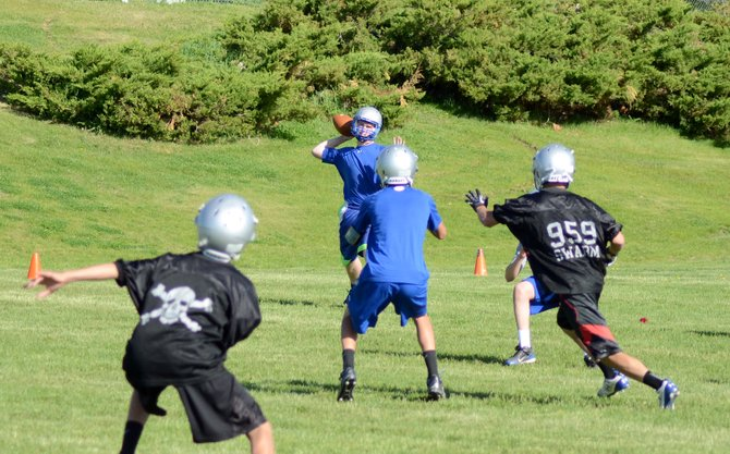 Keenan Hildebrandt winds up to pass to Connor Scranton, center, while defenders swarm to the ball Tuesday morning at the Moffat County practice field. The Bulldogs football team has been working on strength, speed and its offensive and defensive sets to start the summer.