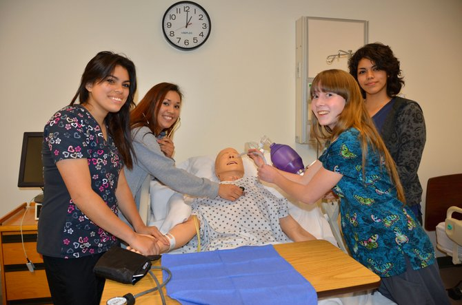 From left, Colorado Northwestern Community College nursing aide students Veronica Clark, Amanda Saenz, Monica Martin and Alma Quintero perform various functions on Simon, a simulation mannequin for CNCC's nursing department. Such equipment allows students to practice medical techniques before moving on to live patients. The school recently received a grant from Caring for Colorado to enhance these aspects of learning.