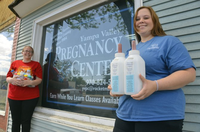 Katie Grobe, executive director of the Yampa Valley Pregnancy Center, left, and volunteer Bethany Longwell hold up the different types of bottles in which they collecting donations for their organization. YVPC will continue the Baby Bottle Fundraiser through Father's Day.
