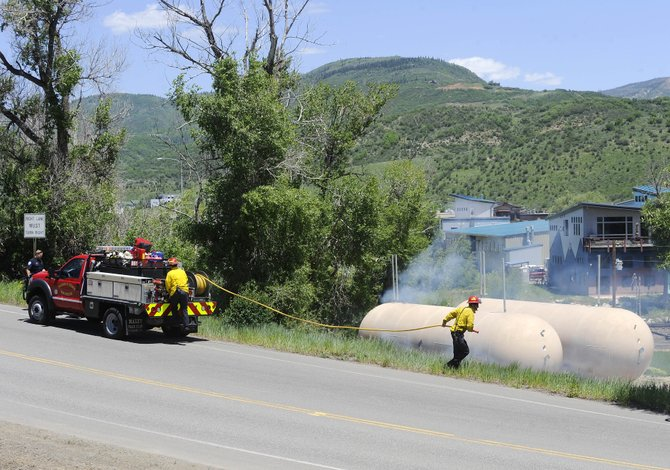 Steamboat Springs Fire Rescue firefighters arrive to put out a small grass fire alongside 13th Street on Friday afternoon.