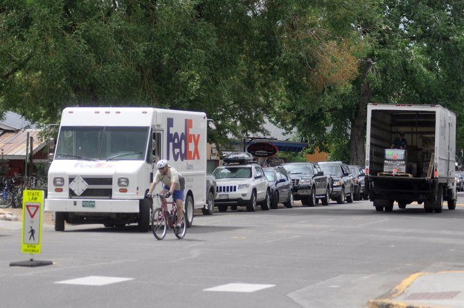 A cyclist rides around two parked delivery trucks and parked cars Monday afternoon on Yampa Street. Several business owners on the street are opposed to removing parking spaces in the area to make it more pedestrian friendly.