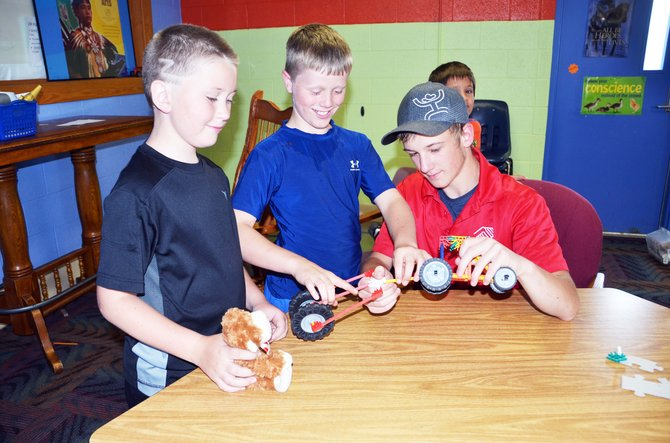 From left, Tyler Marren, Chayton McDonald and staff, Tristin Bailey work together on a project in the Boys & Girls Club game room.