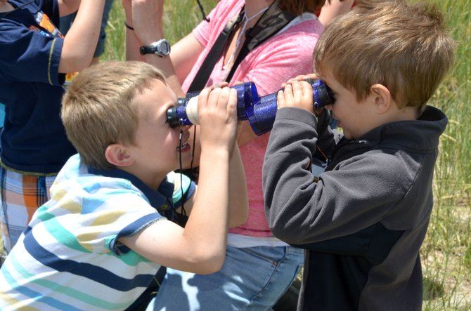 Titus Ruybalid, 6, left, and Oliver Browning, 5, test out their binoculars at close range during the bird-watching portion of Tuesday's class at Wyman Living History Museum's summer nature camp. The weekly activity allows kids ages 4 to 13 to learn about scientific subjects on the museum's property.