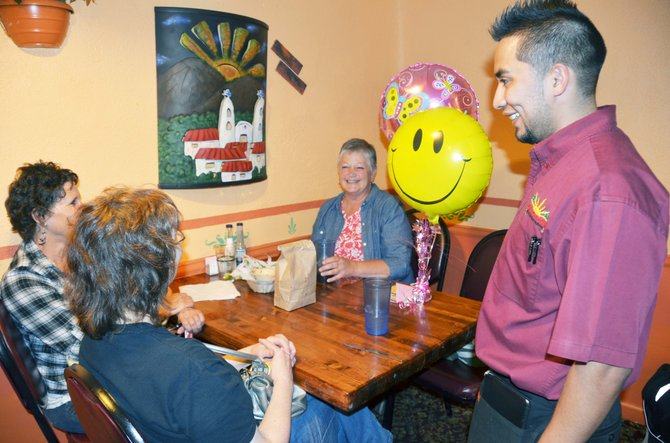 At Vallarta's Restaurant, Macho Nuñez serves guests, from left, Betty McIntyre and Nancy Foster celebrating Mary Morris's birthday — on right.