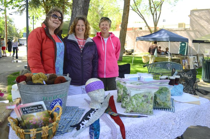 From left, friends Jennifer Stagner, Lorrae Moon and Kim Thompson display their many offerings at Thursday's farmers market in Alice Pleasant Park. The weekly summer event recently started again and will continue in the following months, as will other happenings in downtown Craig.