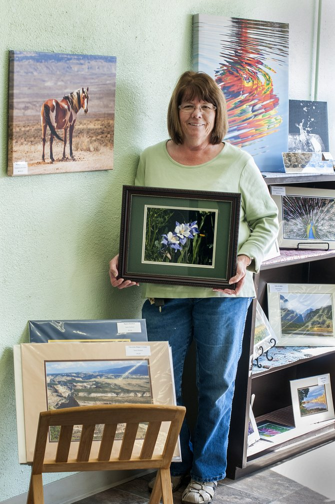 Craig resident and photographer Patti Mosbey holds one of her photographs that will be on display at the pop-up gallery, surrounded by fellow artist Janele Husband's photographs, which also will be on display.