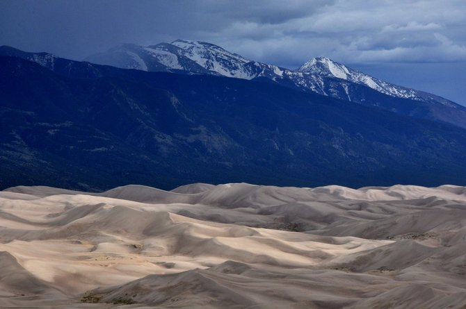 Here's your view at the end of a rigorous 2.3-mile hike on the Sand Ramp Trail in Great Sand Dunes National Park. Sunlight breaks through storm clouds to illuminate the dunes as tall mountain peaks loom beyond.