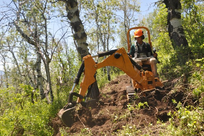 Marc Sehler drives a new singletrack trail-building machine as it clears brush and stumps from what will become the Morning Gloria Trail on Emerald Mountain.