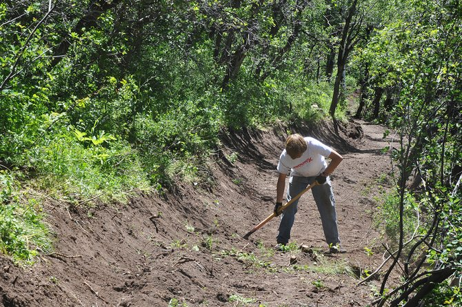 Sam Scully rakes dirt on the Morning Gloria Trail up high on Emerald Mountain. The trail will feature panoramic views of the Yampa Valley and the Flat Tops Wilderness Area.