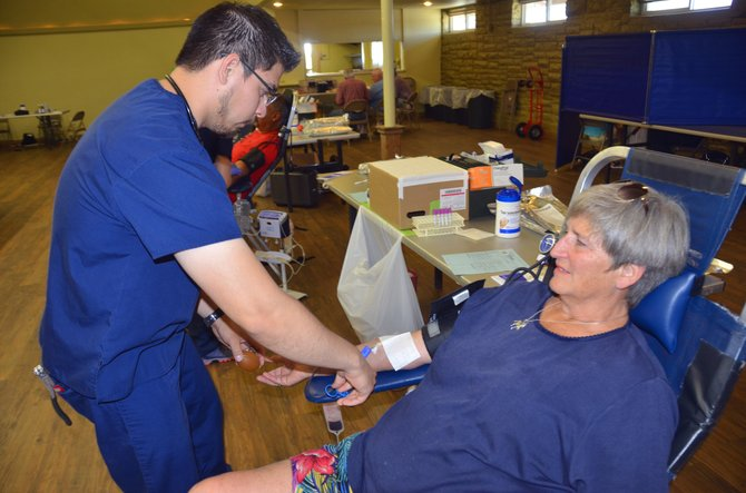 Alex Matus, left, a phlebotomist with Bonfils Blood Center, removes a needle from Craig blood donor Teri Mansfield on Tuesday afternoon at the Moffat County Fairgrounds Pavilion. The organization has been hosting blood drives in Craig for 40 years.
