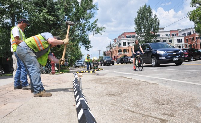 Ty Wisecup hammers in a new temporary curbline on Yampa Street on Wednesday afternoon. The curb was installed to help delineate parking and help keep the bike lane on the street free of parked cars.