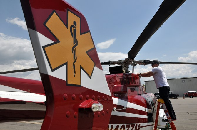 Classic Lifeguard pilot Dave Rasmussen washes the medical helicopter Thursday at Steamboat Springs Airport. The company was called to do about 20 flights last month.