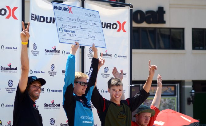 Trevyn Newpher hoists his $500 check for winning the opening weekend of the Enduro-X race series at the downhill park at Steamboat Ski Area.