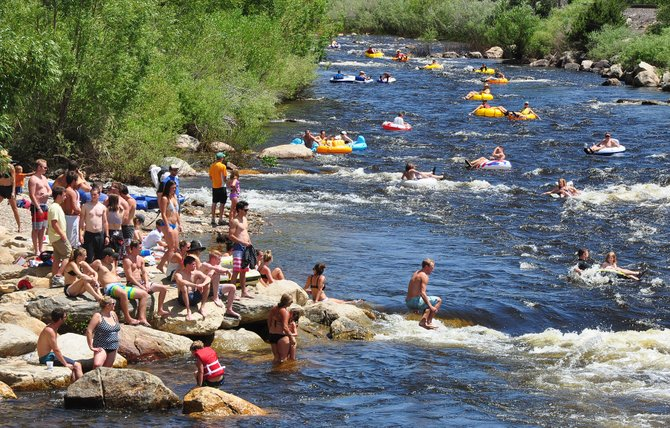 Tubers and sunbathers enjoy a sunny day near Charlie's Hole this summer on the Yampa River.