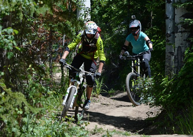 Nicole Miller follows Steamboat Bike Park instructor Andrew Burns' tips as she navigates turns on the Wrangler Gulch trail.