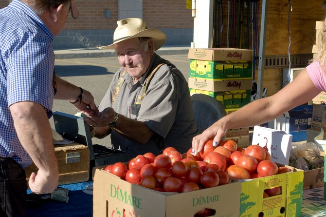 Bill DeVries settles up with a customer at his farm market stand at Walgreens in Craig on Wednesday. DeVries has been bringing his produce to Craig every week for 45 years.