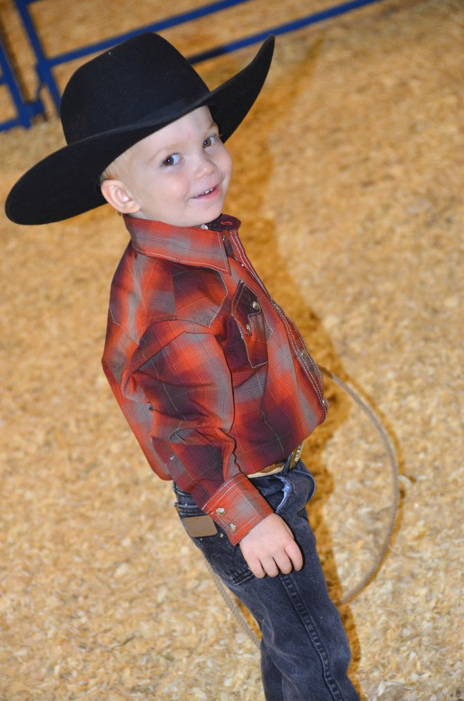 Austin Jazwick, 3, smiles at the audience of the Cowboy Baby Contest on Saturday at the Moffat County Fair. Jazwick was named Future Roping Champ, with other competitors receiving similar titles.