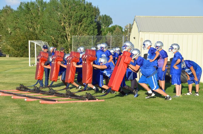 Moffat County High School linemen drag out a blocking sled Monday evening during the first day of practice for the MCHS football team. The team has an entirely new coaching staff, including head coach Keith Gille and Athletics and Activities Director Mike Mitchell.