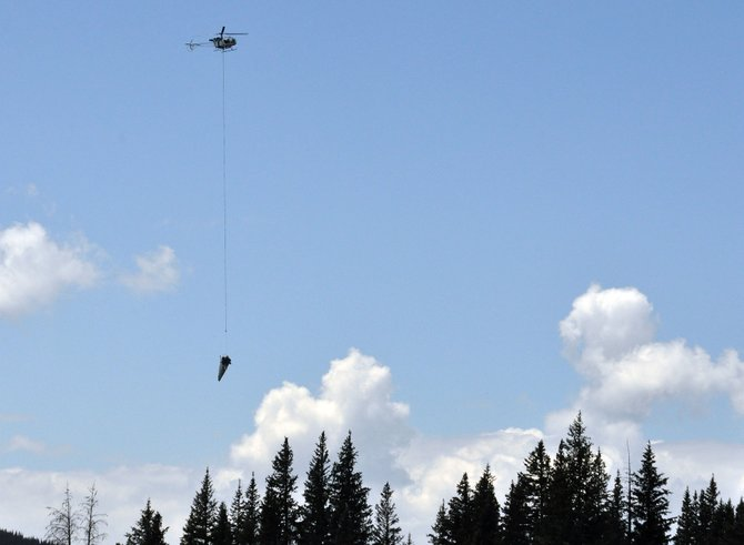 A helicopter carries the fuselage of a plane that crashed Aug. 9 on Rabbit Ears Pass.