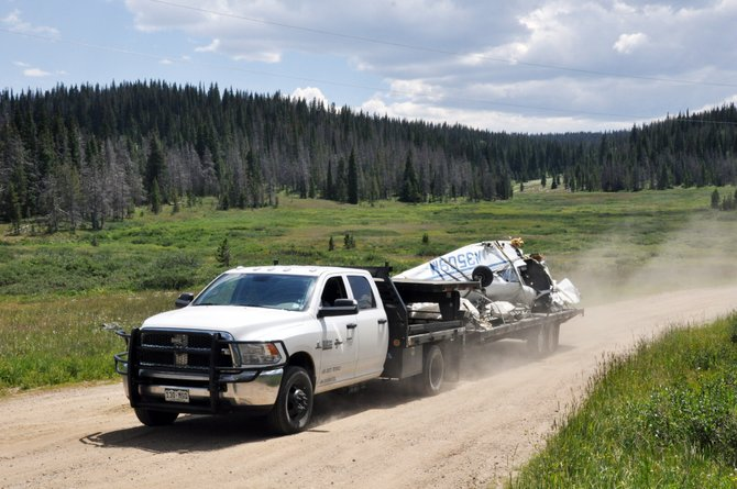 The wreckage of a single-engine Piper Arrow that crashed Saturday on Rabbit Ears Pass is transported away from the area on a trailer Tuesday afternoon. The wreckage was removed from the remote crash site by a helicopter.