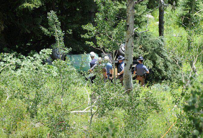 Investigators and rescuers work Tuesday at the site of a fatal car crash on Buffalo Pass.