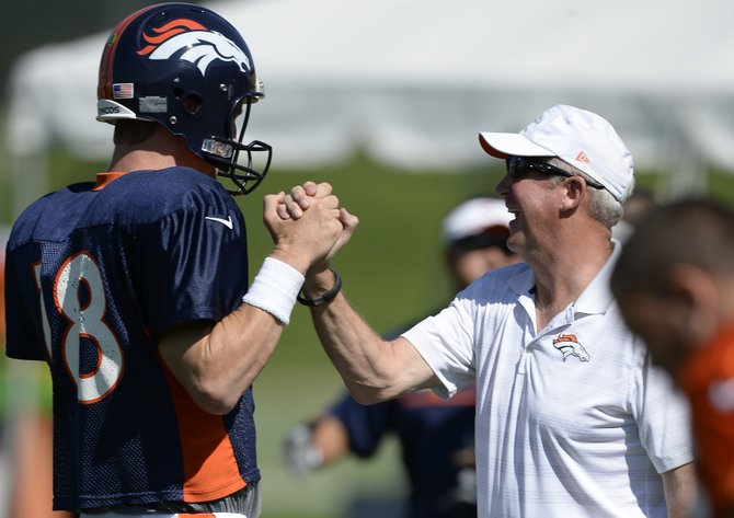 Denver Broncos quarterback Peyton Manning get a high-five from Denver Broncos head coach John Fox before the start of practice at the 2014 training camp Monday at Dove Valley.