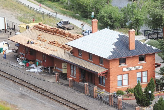 Employees of Wilson Roofing work on top of the Depot Art Center earlier this week. The new roof is part of a $250,000 improvement project to update the building and also makes the building look more like it did when it was built in 1909.