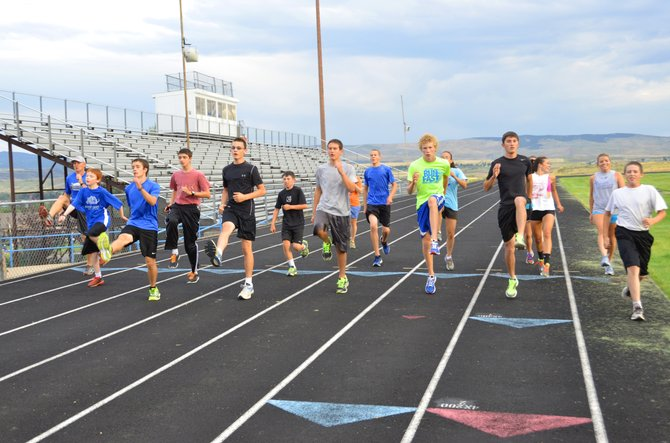 Coach Todd Trapp, far left, leads the Moffat County High School cross-country team in a running drill with leg lifts Tuesday at the MCHS track. The field of runners for the boys and girls teams is tallied at 18.