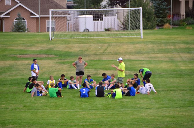 The members of the Moffat County High School boys soccer team convene midfield with coach Harry Tripp during a practice session at the MCHS field. The boys and girls soccer teams will use the site for practices and games after years of playing at other locations across Craig.