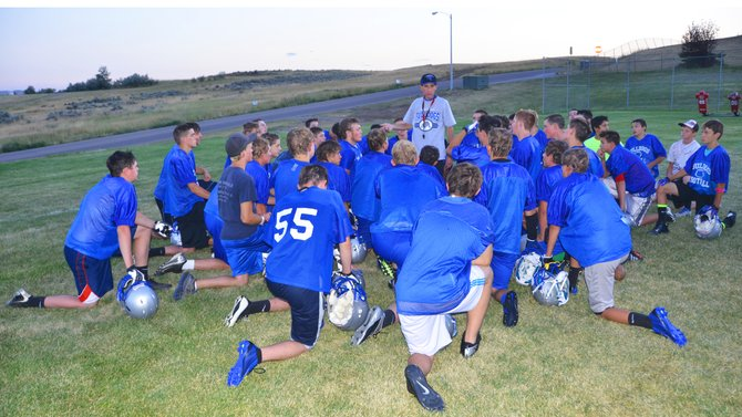 The members of the Moffat County High School football team take a knee to listen to head coach Keith Gille following an evening practice. The team opened its season Friday with a game in Rifle and next will travel to Steamboat Springs on Aug. 29.