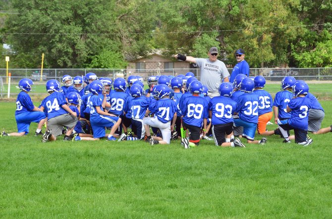 The seventh- and eighth-grade football players of Craig Middle School take heed of coaches Norm Yoast and Tony Maneotis. The teams will host Rangely in their first game of the season Thursday.