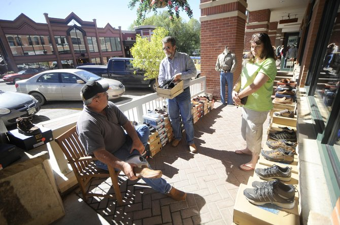 Zirkel Trading owner Steve Hitchcock assists customers Marc and Pam Kelly, of Idaho, during a past sidewalk sale in downtown Steamboat Springs. This Labor Day weekend, businesses will offer sales from Friday through Saturday.