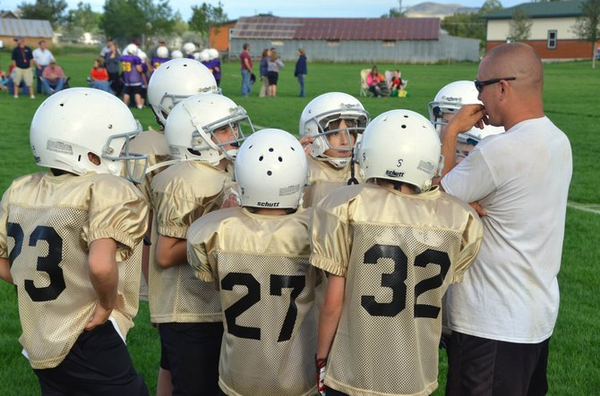 The players of the Boy-Ko Supply Saints gather around Coach Roger Schreck following their first game in the fifth and sixth grade bracket of Craig Parks and Recreation Doak Walker tackle football league at Woodbury Sports Complex. The league's games will continue weekly through October.