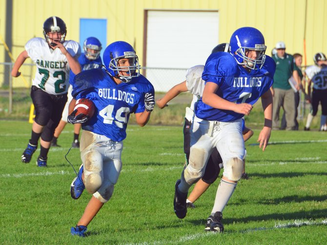 Craig Middle School seventh-grader Landen Najera, right, provides blocking as teammate Kevin Hernandez charges upfield during CMS's Aug. 28 game against Rangely. The team fell 22-6 in the first match of the season.