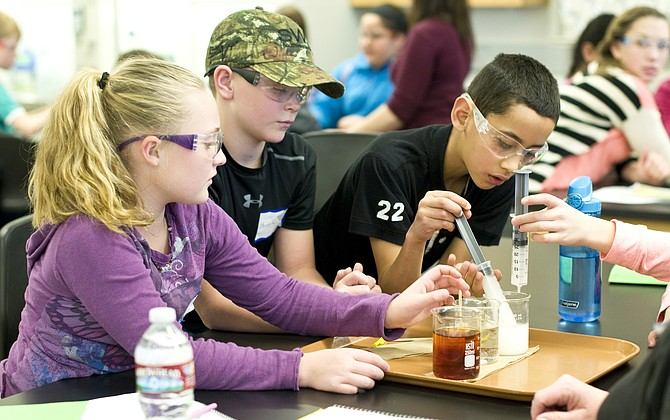 Fourth-graders Madison Caddy, Hunter Kenney and Marcos Romero learn about diffusion through a hands-on experiment involving a cornstarch solution, a thin membrane and a darkly-colored iodine solution. They were among 80 total Moffat County students who participated in University of Colorado Boulder's Science Discovery STEM workshop on Thursday at Colorado Northwestern Community College.