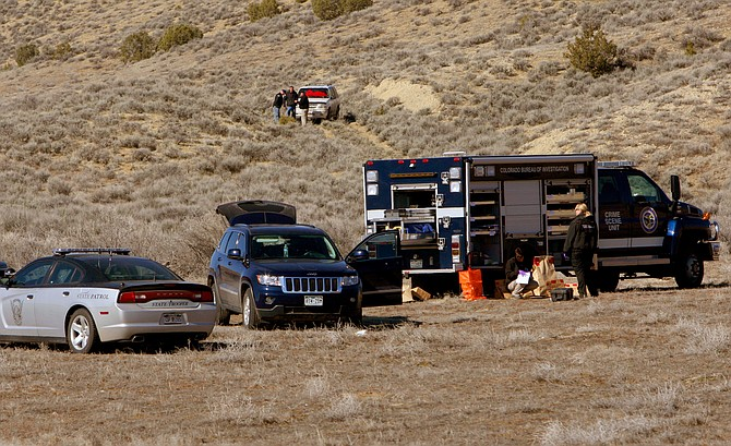 Members of the 14th Judicial District's Critical Incident Response Team examine the scene of an officer-involved shooting resulting in one fatality Monday afternoon at approximately mile marker 10 on U.S. Highway 40 near Dinosaur. Neither of the two officers involved were injured, while one suspect is dead and the other is in custody. The white SUV on the hillside belonged to the two suspects.
