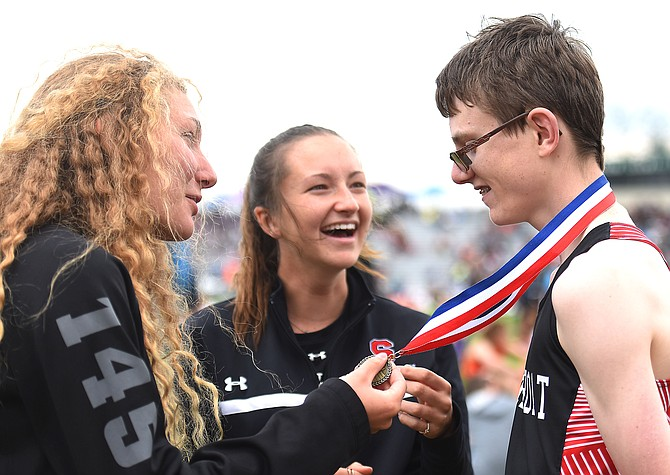 Jon Ruehle shows off the medal he won at the Colorado state track meet in Lakewood on Friday. Friends Kelsey Spognardi and Alex Tumminello worked with Ruehle in school and became close friends with him and spent much of the track season helping him race.