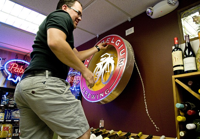 Eastside Liquor owner Ryan Duran takes down a New Belgium sign from his store after pulling the company's beer from his shelves. Duran is one of several liquor store owners in Craig that are pulling New Belgium products in light of a recent discovery that the Colorado microbrewery is a financial supporter of WildEarth Guardians, the nonprofit organization responsible for a lawsuit directed against two Moffat County coal companies.