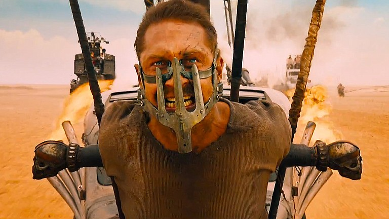 "Max (Tom Hardy) hangs on for dear life while strapped onto the front of a vehicle speeding through the desert in ""Mad Max: Fury Road."" The movie is a sequel to the post-apocalyptic series and is one of film critic Andy Bockelman's selections as one of the best movies of the summer."