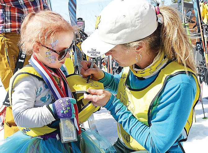 Olympic snowboarder Erin Nemec signs Mara Dawkins' race bid at a celebration for the Sunshine Kids Foundation at the Bashor Bowl picnic area Friday afternoon. Dawkins was one of 25 children who spent the week at Steamboat Ski Area as part of the annual Sunshine Kids Foundation skiing event.