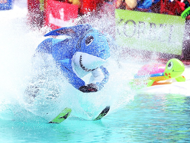 "Brooks Hinkle, dressed as ""Dancing Snow Shark,"" plows through the water during the 2016 Splashdown Pond Skim at Steamboat Ski Area. The event was cancelled this year due to unseasonably warm conditions."