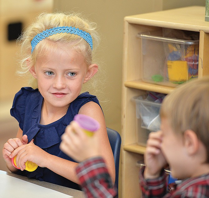 Kindergartner Kenzie Moore looks to a classmate while opening a can of Play-Doh during her first day of class in 2014.