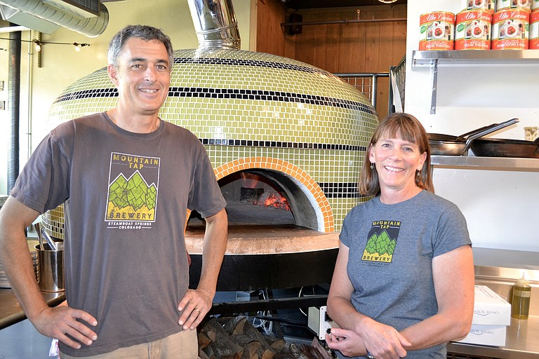 Rich and Wendy Tucciarone, co-owners of Mountain Tap Brewery, stand in front of their 6,000-pound, wood-fired oven.