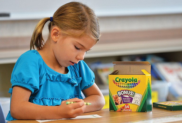 Soda Creek Elementary student Eva Minotto colors on the first day of school in 2014.