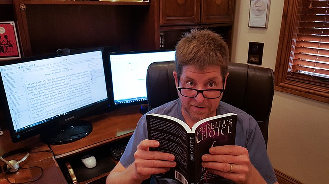 """Author D.A. Hill looks over his award winning novel """"Cerelia's Choice"""" from his basement lair where he works full-time in IT, and part-time as a novelist."""