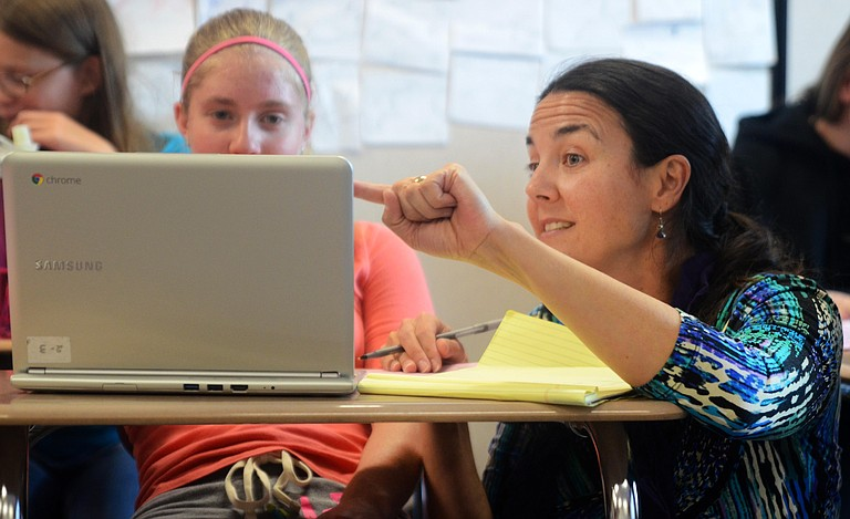 Steamboat Springs High School teacher Meghan Hanson-Peters helps a student with her world geography assignment during class in 2014.