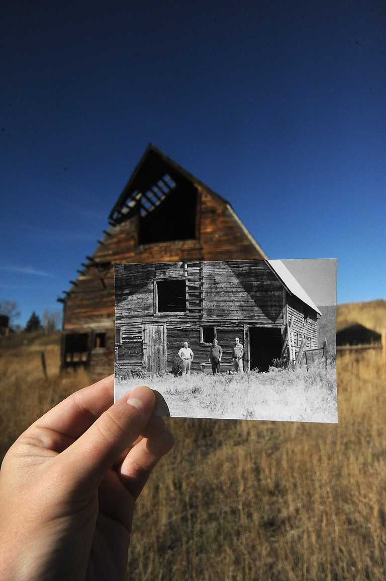 Reporter Scott Franz holds up a photo of the grown up Arnold brothers standing in front of their family's barn during a visit for a school reunion. Pictured from left are Gerald, Harold and Glenn Arnold.