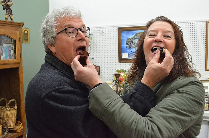 Richard Yager and Eileen Joyce playfully feed each other pieces of Bahamian rum cake at LOVE MI Thrift Shoppe on Saturday during Downtown Business Association's Art Walk and Taste of Chocolate. The annual event includes local art, live music and chocolate dishes at downtown shops, as well as Connections 4 Kids' Cherish the Little Things Art Show.