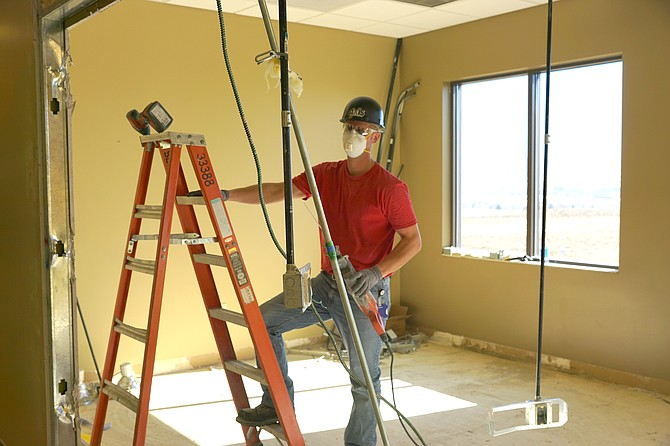 AXIS construction won the bid to remodel the TMH administrative wing into a place for women's health services. While not local, AXIS has hired a number of local companies as subcontractors. Pictured: An Axis builder prepares to work on the ceiling.